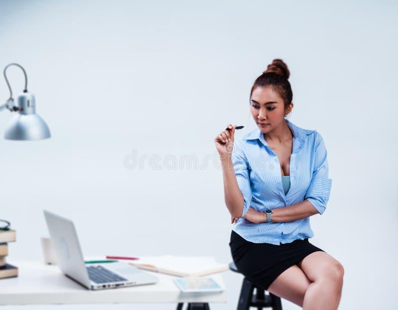 在女商人的选择聚焦在办公室,举行黑色在手中工作,看在桌上 膝上型计算机、Ipad、书和笔投入了  免版税库存照片