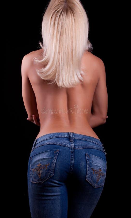 在女孩牛仔裤露胸部的年轻人之后 图库摄影