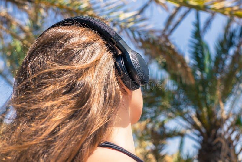 在女孩的后面看法耳机听的音乐步行的在棕榈森林塞舌尔海岛 免版税库存图片