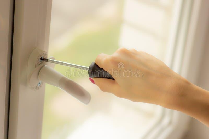 在女孩的手上修理的窗口,特写镜头一把螺丝刀 库存图片