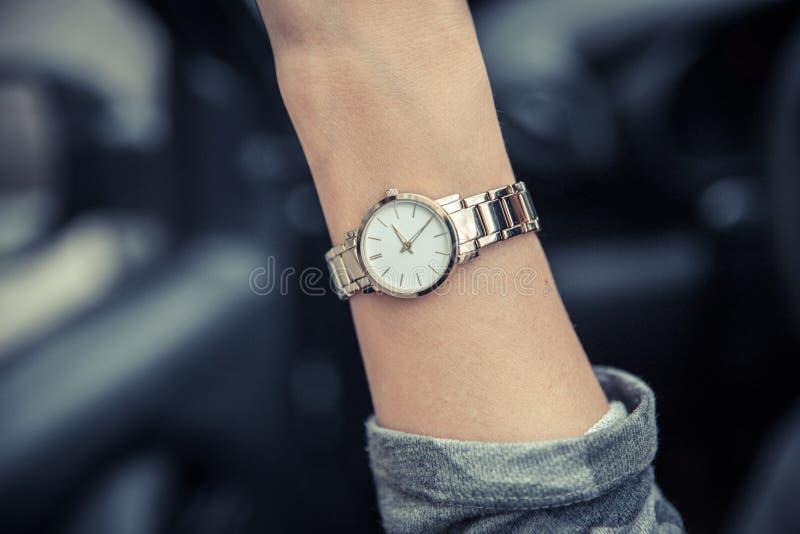 在女孩的手上的妇女的手表 妇女的金表 E 免版税库存照片