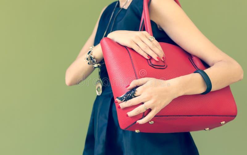 在女孩的肩膀的时兴的美丽的大红色提包时髦一件黑的礼服的 颜色温暖 库存图片
