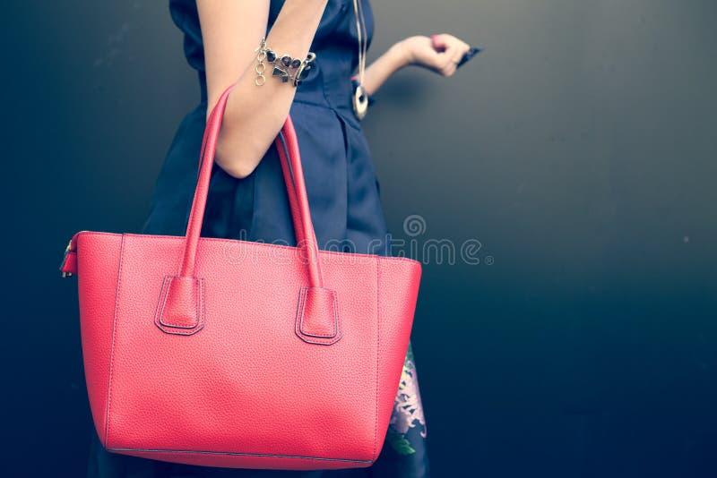 在女孩的胳膊的时兴的美丽的大红色提包一件时兴的黑礼服的,摆在墙壁附近在一个温暖的夏天n 图库摄影