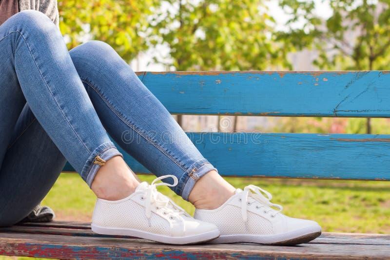在女孩腿的白色运动鞋在蓝色牛仔裤 免版税库存图片