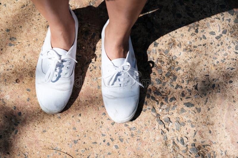 在女孩腿的白色运动鞋 库存照片
