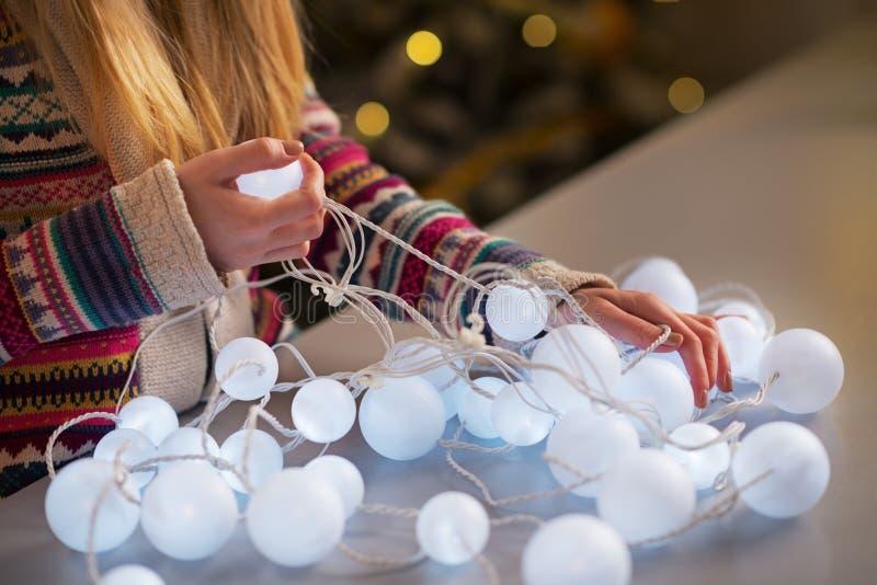 在女孩解开的圣诞灯的特写镜头 免版税库存照片