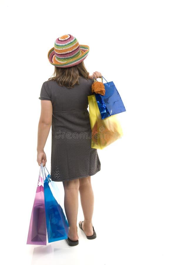 在女孩购物年轻人之后的袋子 免版税库存图片
