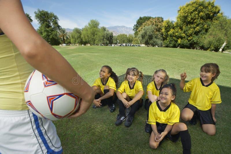 在女孩足球运动员前面的教练 库存图片