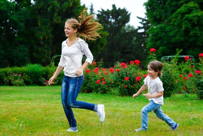 在女孩以后的男孩奔跑 背景兄弟查出的姐妹白色 库存图片