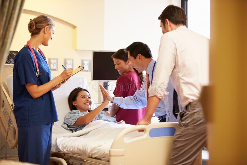 在女性患者附近的医疗队会议在医房 免版税库存照片