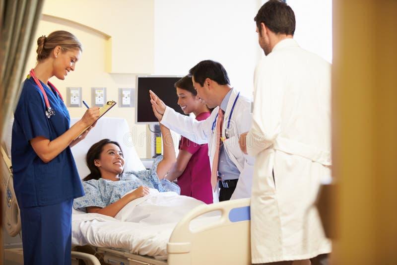 在女性患者附近的医疗队会议在医房 库存照片