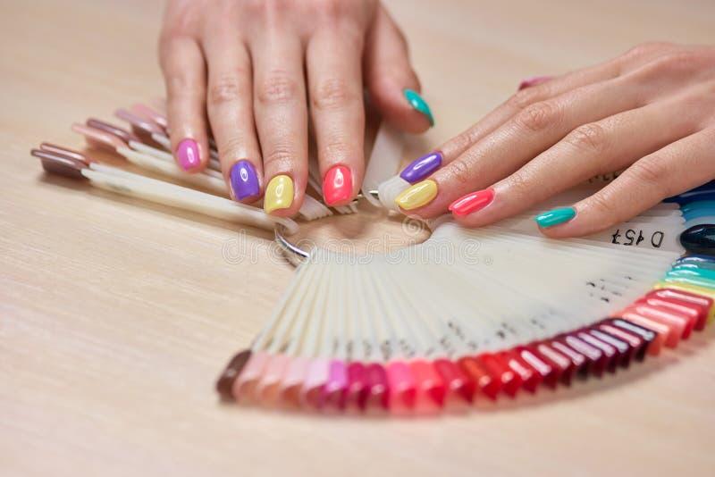 在女性手上的多彩多姿的夏天修指甲 图库摄影