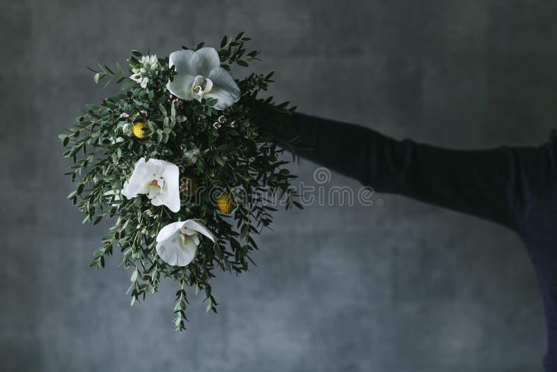 在女性手关闭的兰花花 免版税库存照片