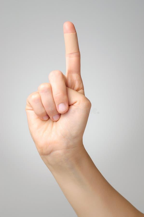 在女性手指的膏药 免版税库存图片