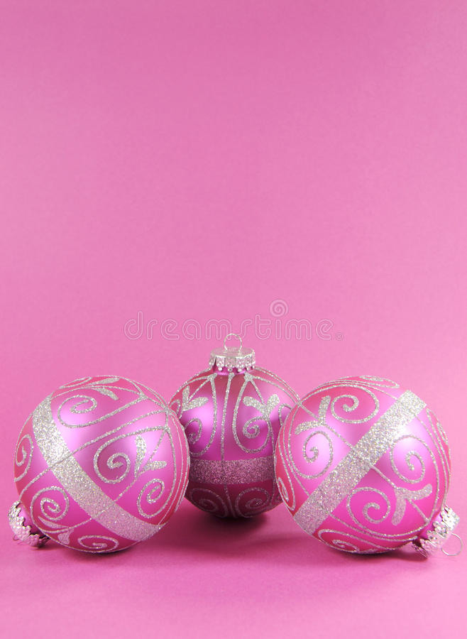 在女性桃红色背景的美丽的紫红色的桃红色欢乐中看不中用的物品装饰品与拷贝空间-垂直 库存图片