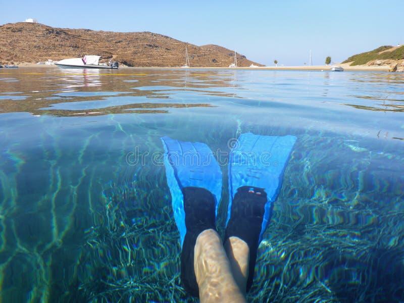 在女性腿的蓝色swimfins在Kolona中透明的水加倍海湾基斯诺斯岛海岛基克拉泽斯希腊,爱琴海 免版税库存图片