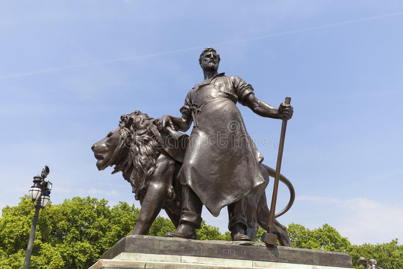 在女王维多利亚纪念品附近的四个古铜色雕象之一,伦敦,英国 库存图片