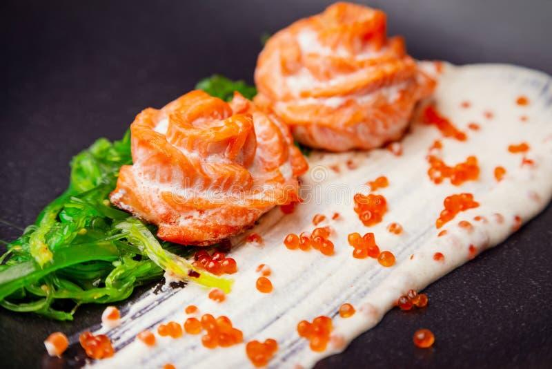 在奶油沙司的煮熟的被烘烤的三文鱼装饰与hiyashi海藻和红色鱼子酱 免版税库存图片