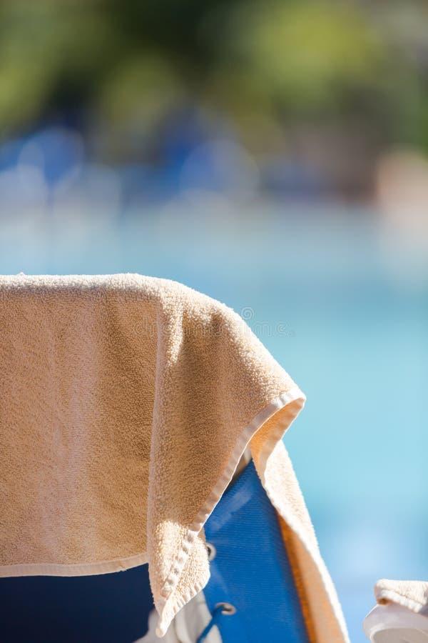 在奶油色颜色的海滩毛巾在空的轻便折叠躺椅垂悬了由s 免版税库存图片