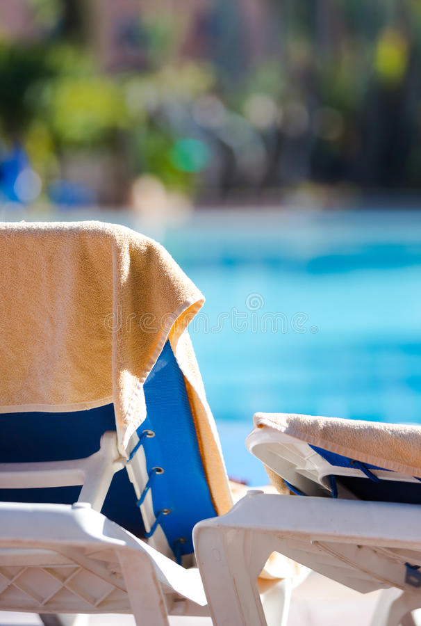 在奶油色颜色的海滩毛巾在空的轻便折叠躺椅垂悬了由s 库存图片