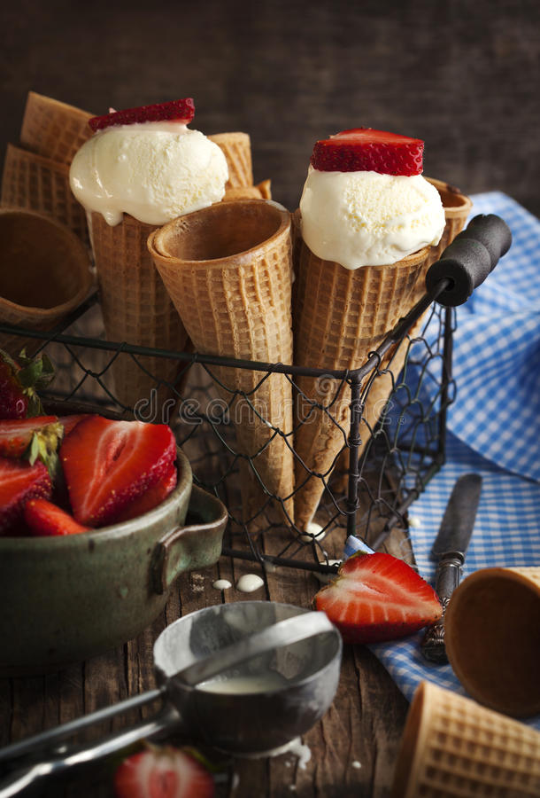 在奶蛋烘饼锥体的香草冰淇淋用草莓 免版税图库摄影