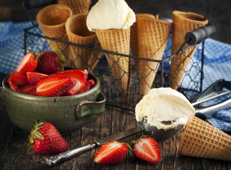 在奶蛋烘饼锥体的香草冰淇淋用草莓 免版税库存照片