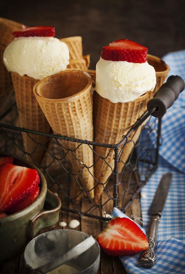 在奶蛋烘饼锥体的香草冰淇淋用草莓 免版税库存图片