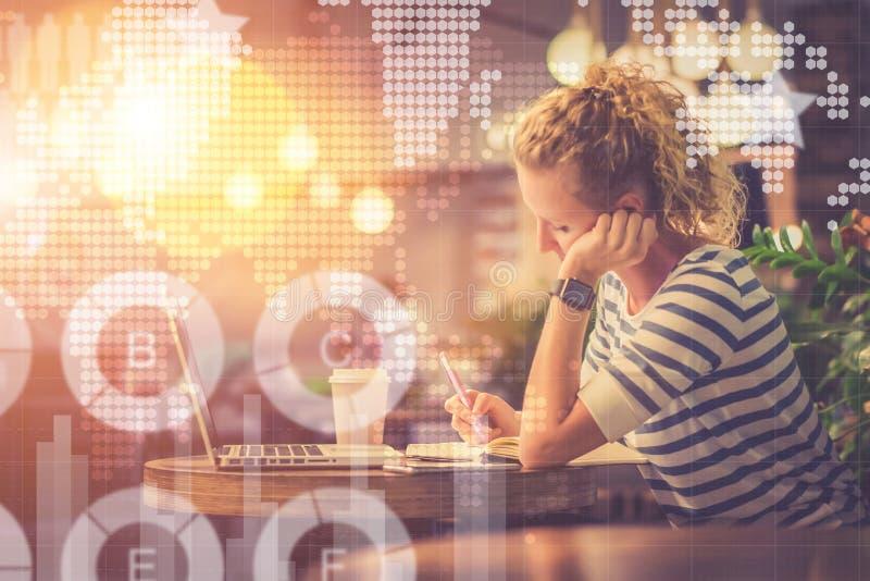 在她前面是膝上型计算机在咖啡旁边 在线了解 执行家庭作业学员 影片作用 图库摄影