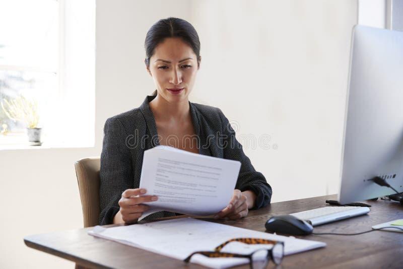 在她的书桌的年轻亚洲妇女读书文件在办公室 库存照片
