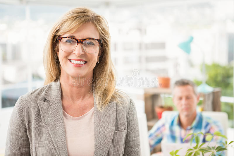 在她的同事前面的微笑的偶然女实业家 图库摄影