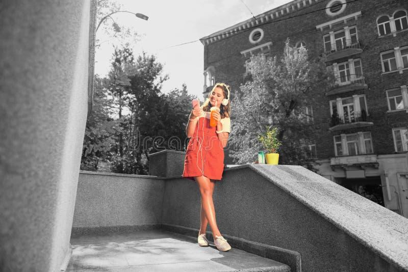 在她的听音乐和饮用的橙汁过去的房子附近的学生身分 免版税库存图片
