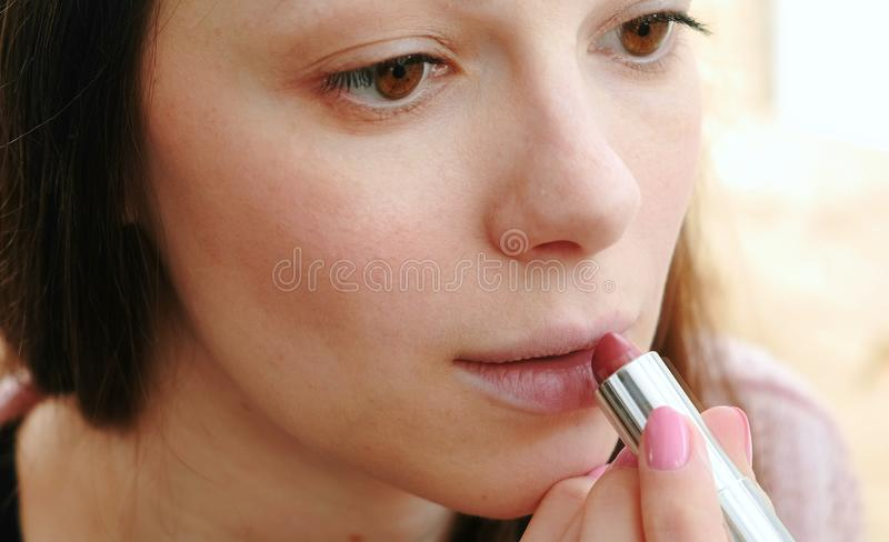 在她的嘴唇上把明亮的唇膏放妇女的特写镜头面孔 库存图片