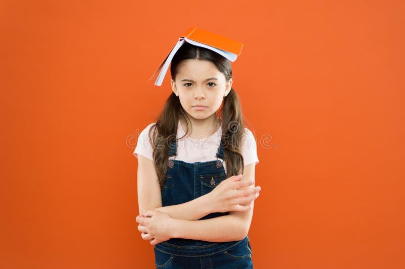 在她的头的书 女孩书屋顶头 小女孩书橙色背景 孩子的有趣故事 学习和 免版税库存照片