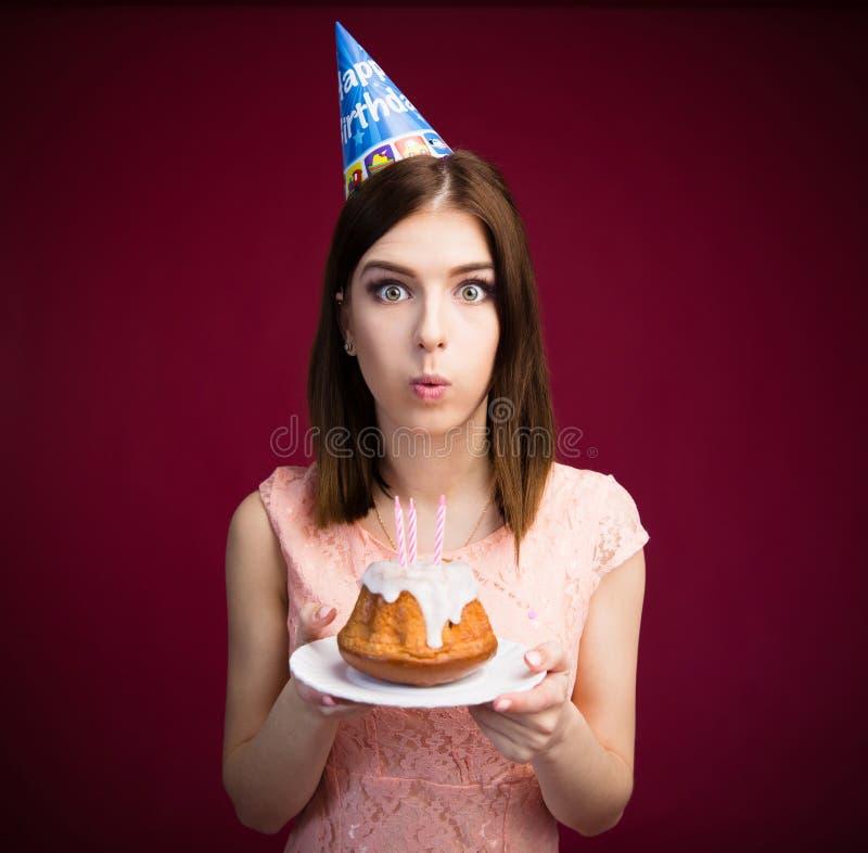 在她的少妇吹的蜡烛蛋糕 图库摄影