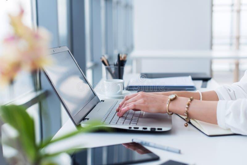 在她的工作场所的女性撰稿人,家,写新的文本使用膝上型计算机和Wi-Fi互联网连接早晨 免版税库存照片