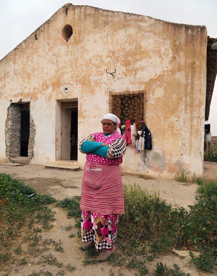 在她的房子前面的一个中年巴巴里人妇女身分有在她的面孔的一个反抗表示的 免版税库存图片