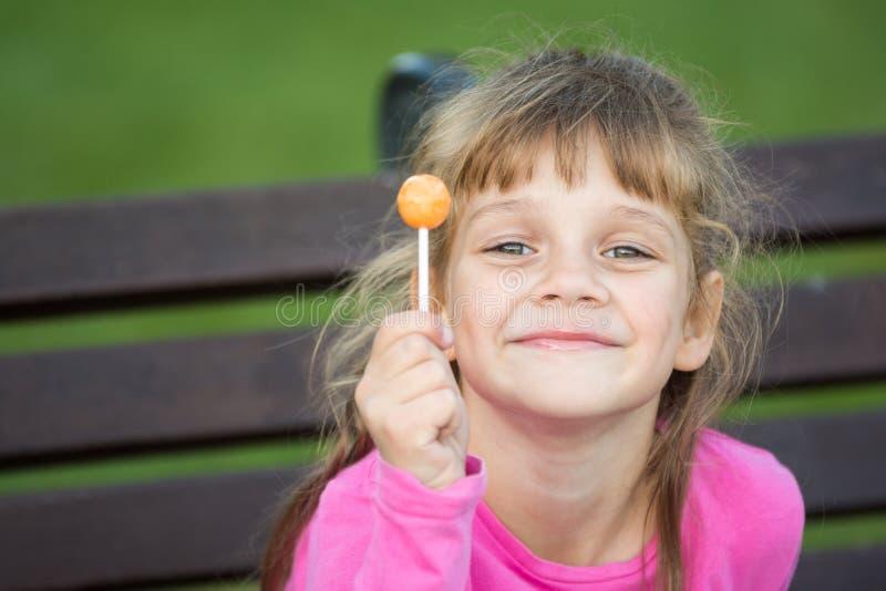 在她的手上拿着一个棒棒糖一个六岁的快乐的女孩的画象 免版税库存照片