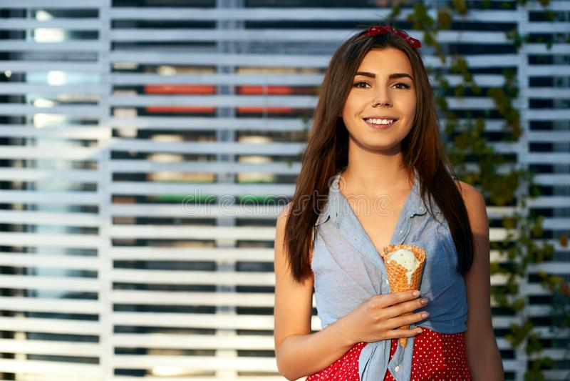 在她的手上拿着冰淇凌和看照相机的少妇画象 吃可口香草的深色的女孩 图库摄影