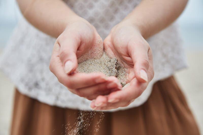 在她的手外面的女孩倾吐的沙子 库存照片