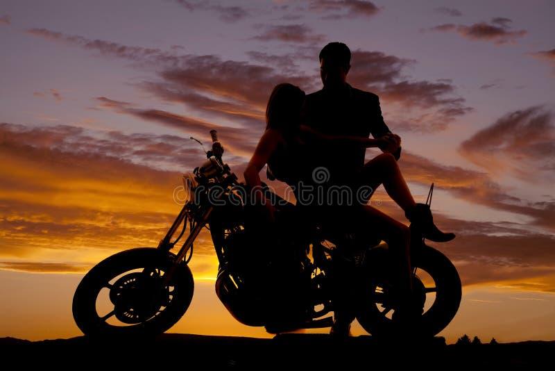在她的摩托车的夫妇倾斜他举行 库存照片