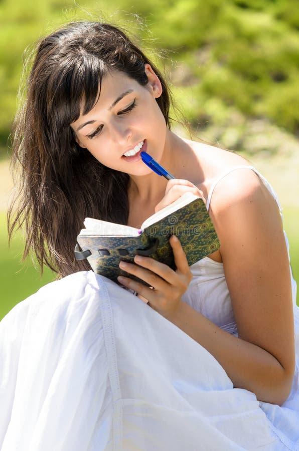 在她的日志的俏丽的女孩读取和文字 库存图片