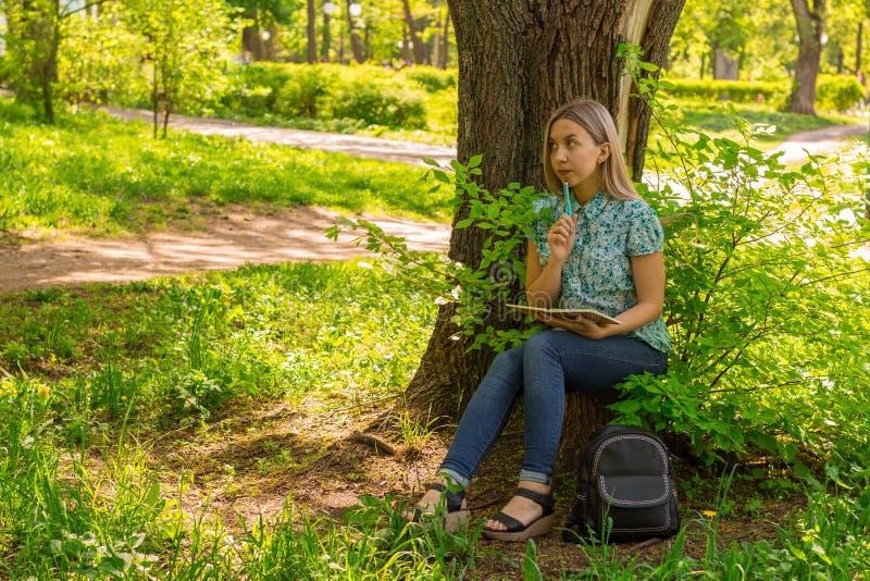 在她的日志的美好的少妇文字在公园 免版税库存图片