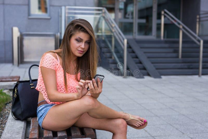 在她的智能手机的年轻俏丽的女孩文字消息 都市backg 免版税库存图片