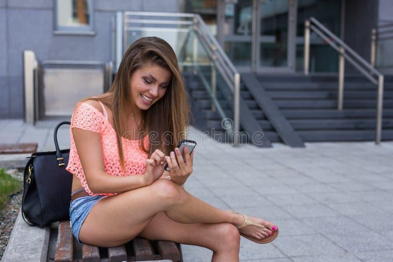 在她的智能手机的年轻俏丽的女孩文字消息 库存图片