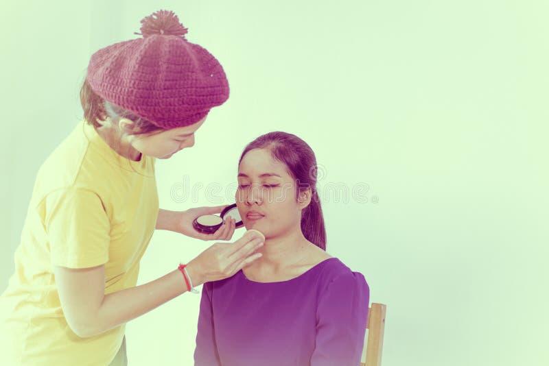 在她的朋友的化妆师工作 真正的人民,女孩得到脸红o 免版税库存图片