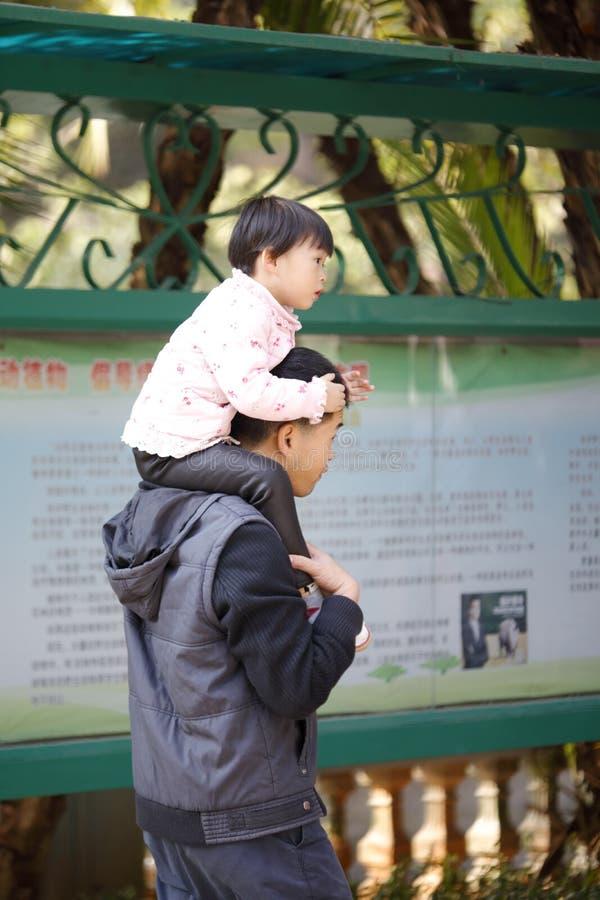 在她的父亲` s脖子的女儿骑马,多孔黏土rgb 库存图片