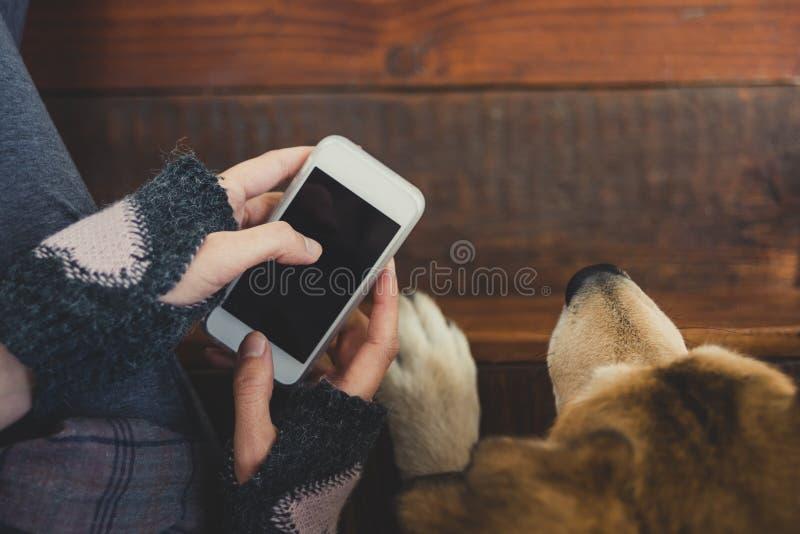在她的狗旁边的女孩选址使用智能手机 免版税库存图片