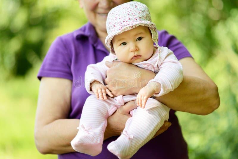 在她的祖母的手上的女婴 免版税图库摄影