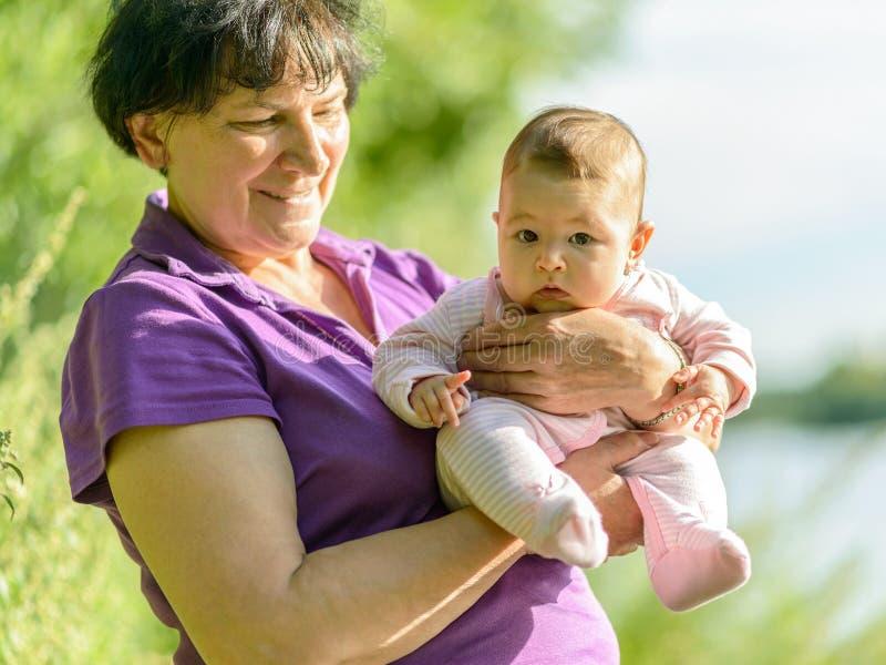 在她的祖母的手上的女婴 库存照片