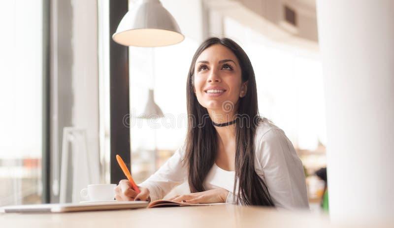 在她的笔记本和饮用的早晨咖啡的少妇文字 库存照片